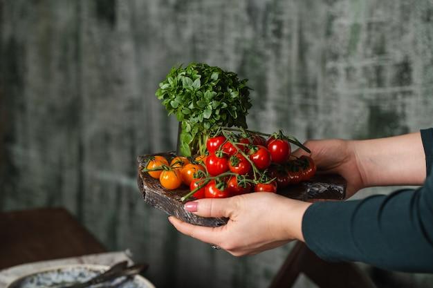 Osoba niosąca tacę z różnymi warzywami