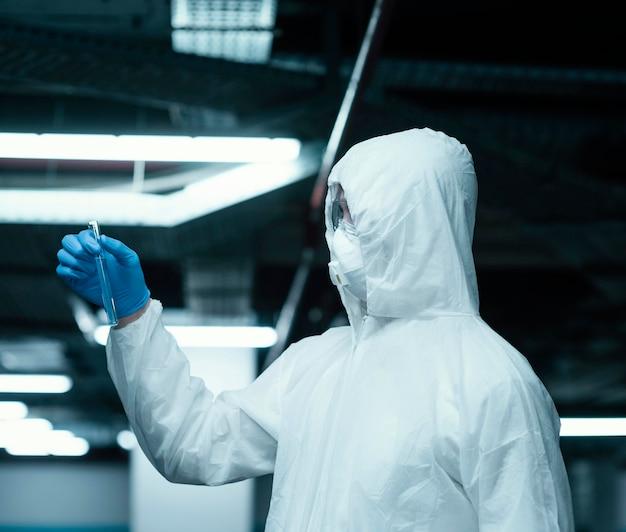 Osoba nosząca kombinezon ochronny i pobierająca próbki