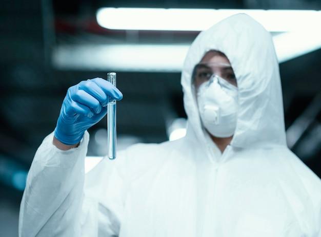 Osoba nosząca kombinezon ochronny podczas pobierania próbek