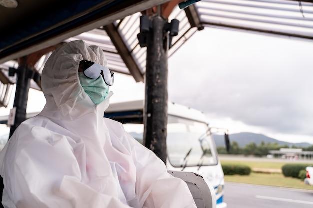 Osoba nosząca kombinezon ochronny, śoi z maską, siedzi w autobusie i wjeżdża na parking przed terminalem