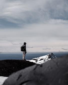 Osoba nosząca plecak stojący na szczycie góry pod pochmurnym niebem