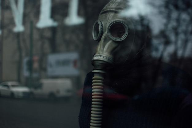 Osoba nosząca respirator stojący za szkłem