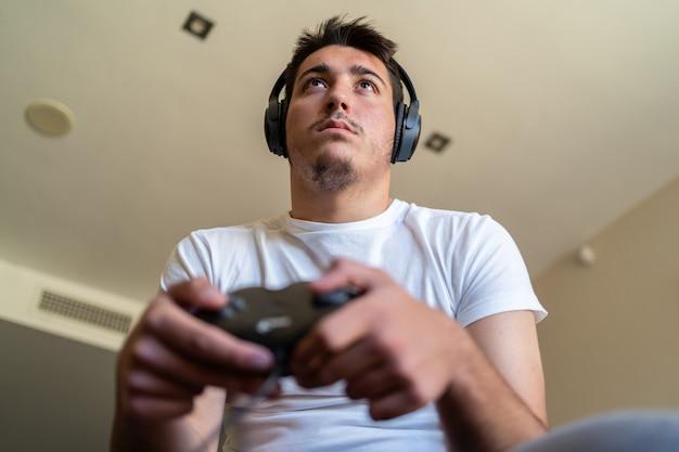 Osoba nosząca słuchawki i grająca w gry wideo w telewizji