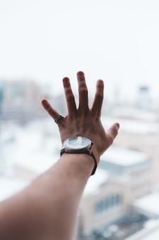 Osoba nosząca srebrny okrągły zegarek analogowy ze srebrną bransoletą z linkami