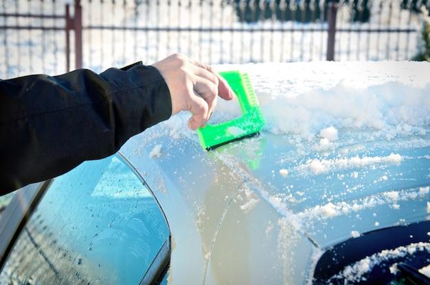 Osoba odgarnianie śniegu z jego samochód