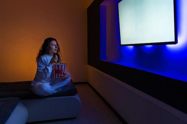 Osoba ogląda film siedząc na kanapie z kubełkiem popcornu