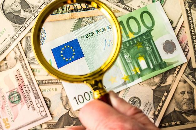 Osoba oglądająca banknot euro na rachunkach w dolarach amerykańskich z lupą