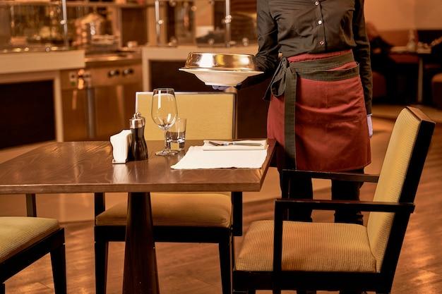 Osoba opuszczająca przykryte naczynie na stole ze sztućcami