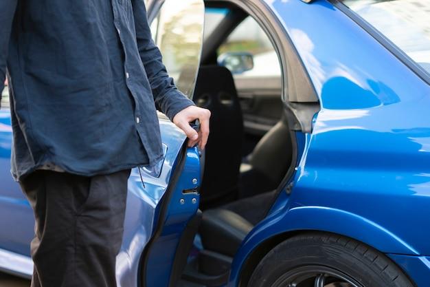 Osoba otwiera niebieskie drzwi samochodu i siada w środku, rozpoczyna się automatyczna podróż