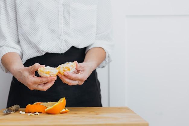 Osoba otwierająca obraną pomarańczę