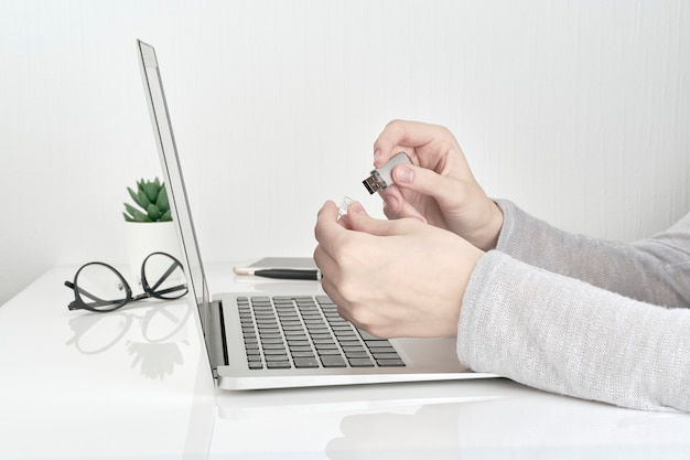 Osoba otwierająca usb flash obok laptopa, koncepcja pracy biurowej