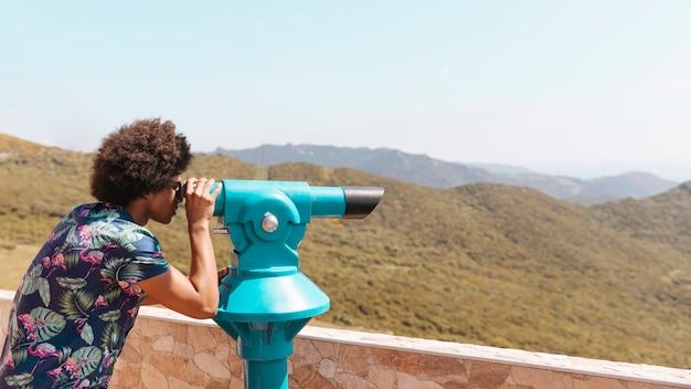Osoba patrząc na krajobraz przez lunetę