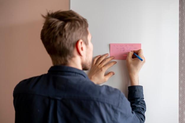 Osoba pisze tekst przypomnienia na naklejce z notatką na lodówce