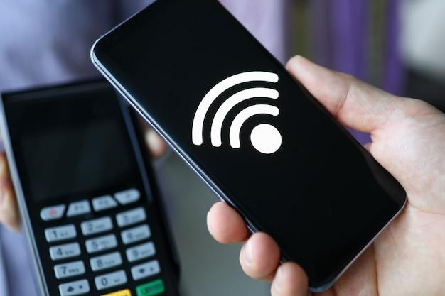 Osoba płaci za zakup za pomocą aplikacji mobilnej