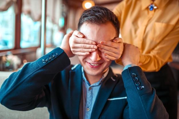Osoba płci żeńskiej zamyka oczy ręce do mężczyzny w restauracji. romantyczna randka zakochanej pary