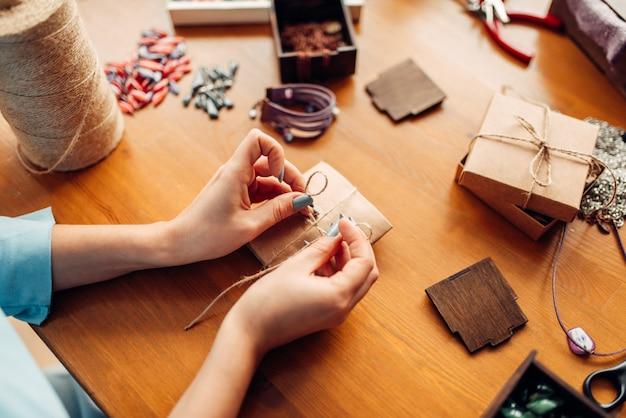 Osoba płci żeńskiej zawiązuje łuk na pudełku prezentowym, robótki ręczne