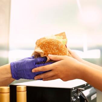 Osoba pobierająca hamburgera od pracownika fast food