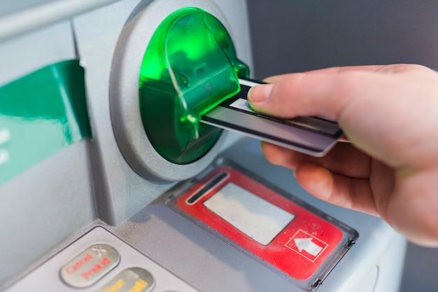 Osoba pobierająca pieniądze z bankomatu