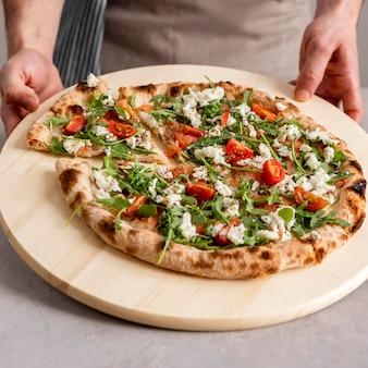 Osoba pod wysokim kątem chwytająca kawałek świeżej pizzy