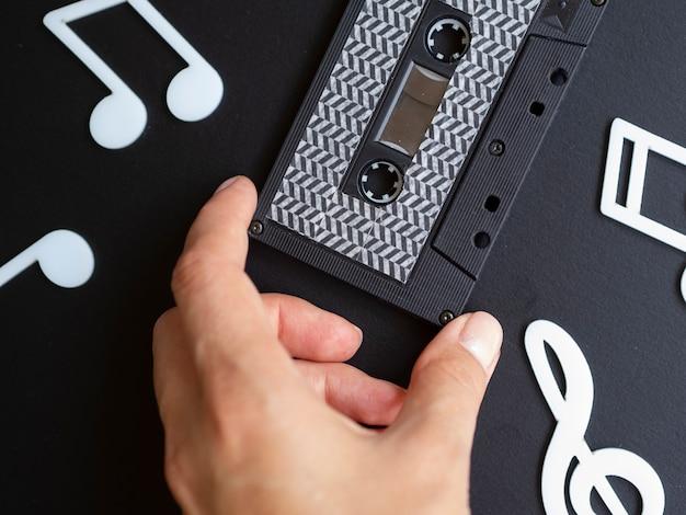 Osoba posiadająca czarny nowoczesny kaseta magnetofonowa