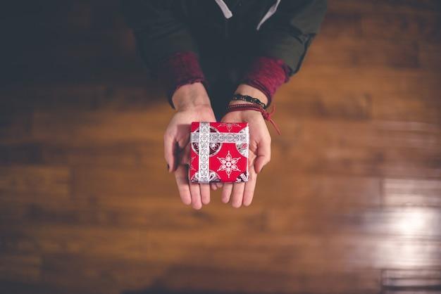 Osoba posiadająca czerwone i białe pudełko
