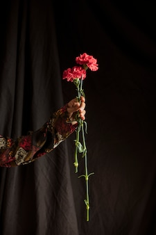 Osoba posiadająca czerwone kwiaty goździka