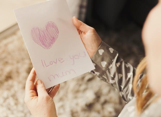 Osoba posiadająca kartkę z życzeniami z i love you mama napis