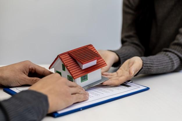 Osoba posiadająca mały dom modelowy jest jak dostawa do domu, kupujący zawarł umowę kupna-sprzedaży domu z projektem mieszkaniowym z podpisaną umową. pomysły na handel nieruchomościami.