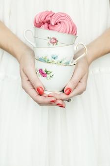 Osoba posiadająca trzy filiżanki ceramiczne kwiatowe