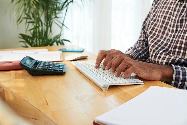 Osoba pracująca na jego biurku