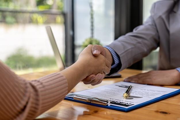 Osoba prowadząca rozmowę kwalifikacyjną i kandydat do pracy trzymają się za ręce po zakończeniu rozmowy kwalifikacyjnej. koncepcja rekrutacji pracowników do pracy w firmie, wolne stanowiska.