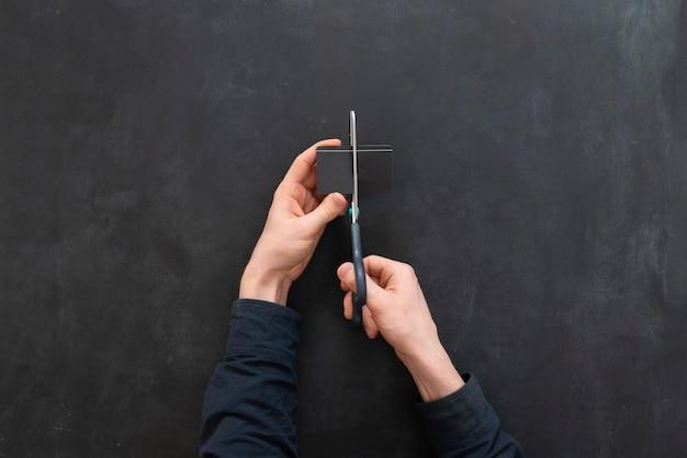 Osoba przecięła kartę kredytową nożyczkami. problem bankructwa i utraty pieniędzy