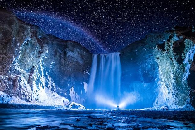 Osoba przed wodospadami w nocy