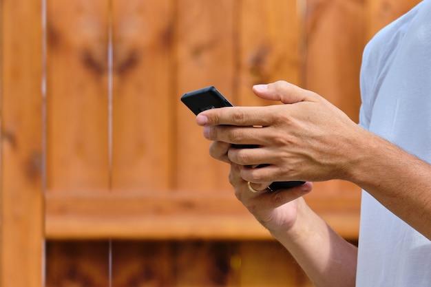 Osoba przewija rękę w smartfonie na ulicy