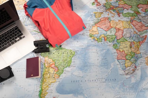 Osoba przygotowująca podróż z laptopem, lornetką, kurtką i paszportem na mapie świata.