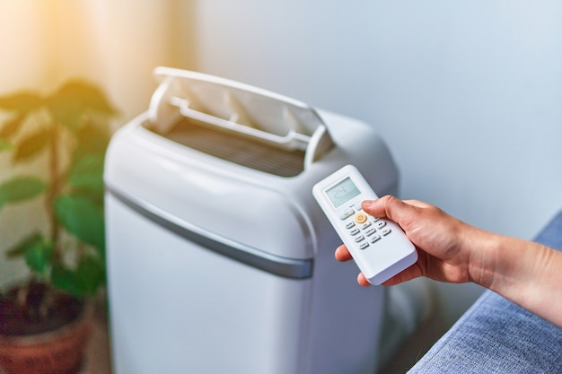 Osoba reguluje temperaturę chłodzenia klimatyzatora w domu za pomocą pilota w gorące letnie dni