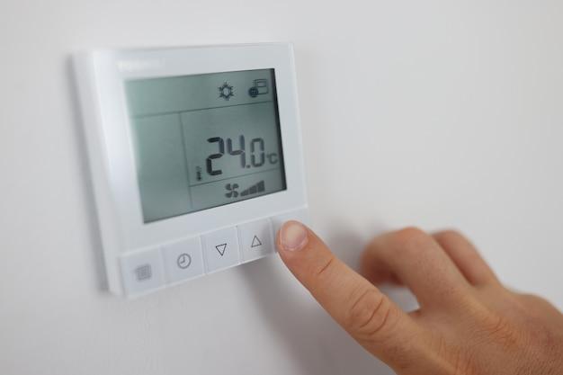 Osoba reguluje temperaturę powietrza w pomieszczeniu za pomocą pilota na ścianie koncepcji sterowania klimatem