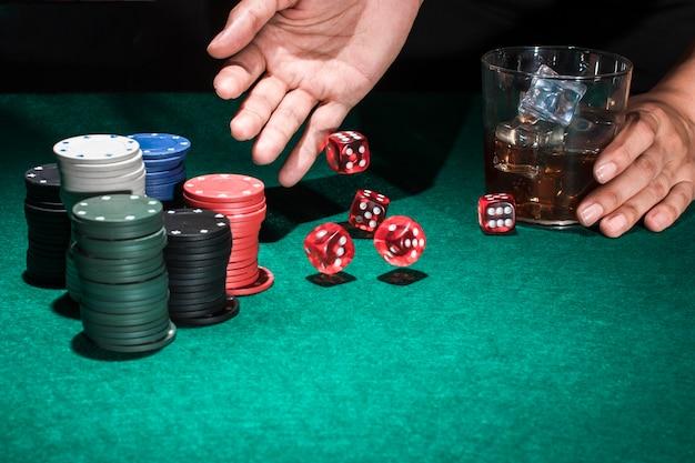 Osoba ręka trzyma szkło whisky podczas gdy toczni czerwoni kostka do gry