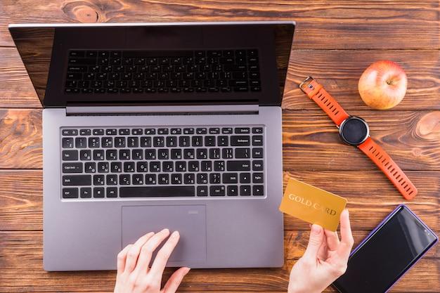Osoba ręka za pomocą złota karta na zakupy online z laptopem na drewnianym stole