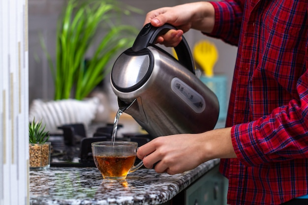 Osoba robi herbatę przy użyciu wrzącej wody z czajnika elektrycznego w kuchni w domu. czas na śniadanie