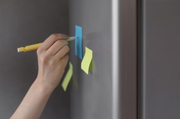 Osoba robi notatki na naklejce na lodówce jako przypomnienie z telefonu