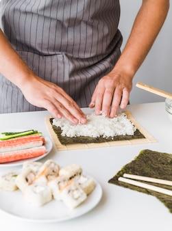 Osoba rozkładająca ryż na nori