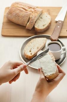 Osoba rozprowadza miękki zsiadły chleb na chlebie