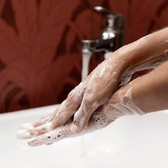 Osoba siedząca na boku myjąca ręce mydłem w postaci stałej