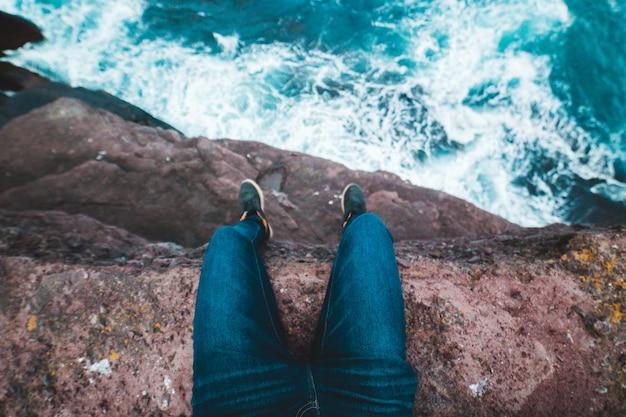 Osoba siedząca na klifie