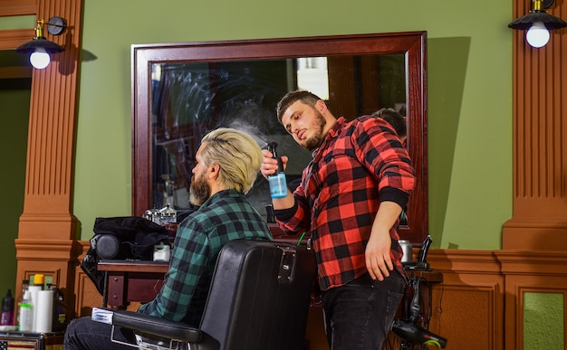 Osoba siedząca na krześle hydraulicznym. odwiedź fryzjera. utrzymanie kształtu. mężczyzna w salonie fryzjerskim. klient fryzjera. pielęgnacja brody. usługi fryzjerskie. idealny wygląd. zarost. przystojny hipster.