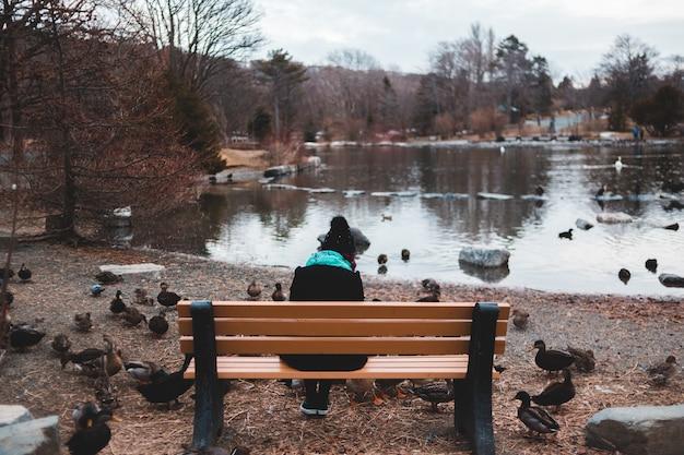 Osoba siedząca na ławce obok zbiornika wodnego