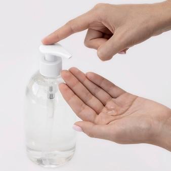 Osoba siedząca pod dużym kątem używająca mydła w płynie z butelki
