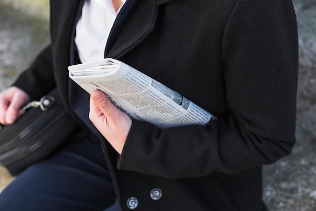 Osoba siedząca z gazetą na zewnątrz