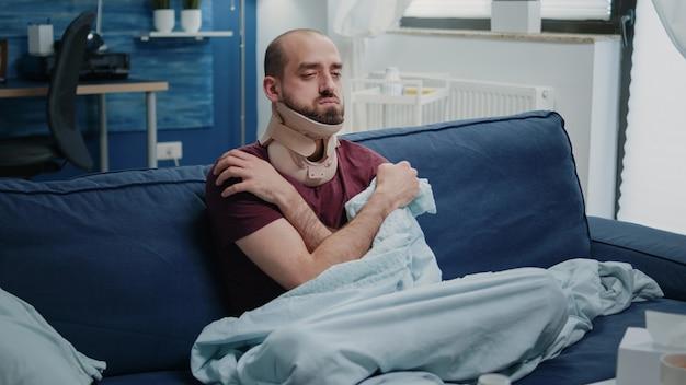 Osoba siedząca z pianką na szyję po urazie mięśnia